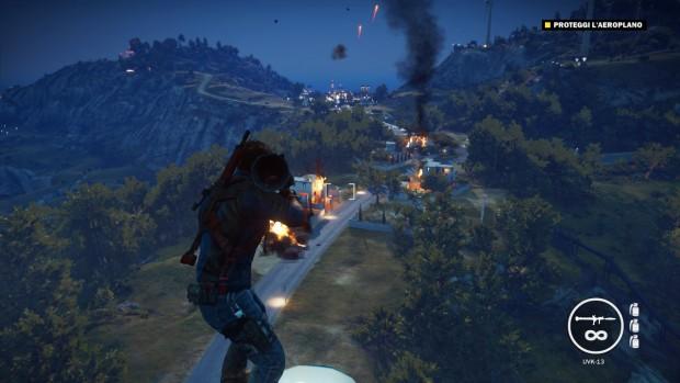 Il nostro protagonista imbraccia un'arma puntata contro edifici in fiamme ed esplosioni, nella notte.