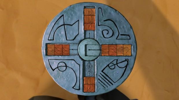 Armikrog: immagine di un disco visto dall'alto con delle iscrizioni nei 4 quadranti, quella in basso a destra sembra una testa di pesce.