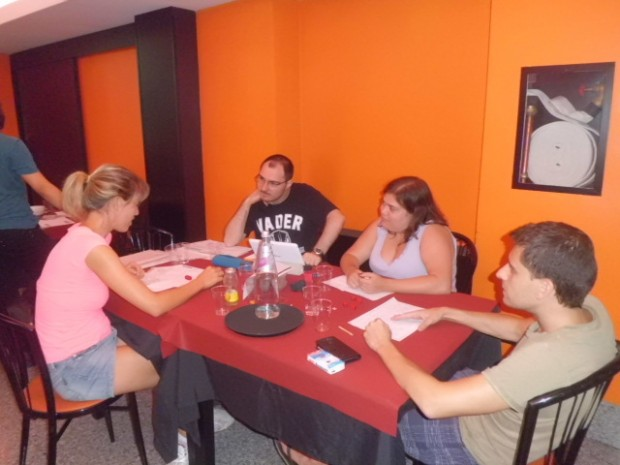 Alcune persone sedute attorno ad un tavolo, stanno tutti osservando con attenzione una di loro.